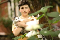 Teenager boy with cat in hummock nap royalty free stock images