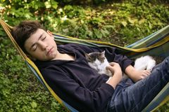 Teenager boy with cat in hummock nap stock images