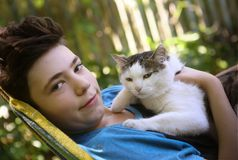 Teenager boy with cat in hummock nap stock image