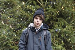 Teenager boy with a Christmas tree in the background. Teenager boy with anorak and a black cap looking at camera with a Christmas tree in the background royalty free stock images