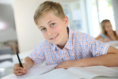 Teenager boy in class wiritng. Portrait of 12-year-old boy in classroom Royalty Free Stock Photo