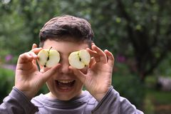 Teenager boy close up portrait with cut apple eyes. On green garden background Royalty Free Stock Photos