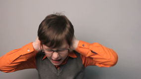 Teenager boy closed his ears with his hands loud
