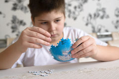 Teenager boy collects puzzles from Globe Stock Photo