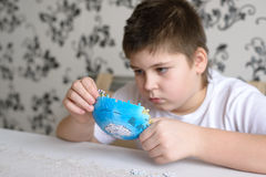 Teenager boy collects puzzles from Globe Royalty Free Stock Image