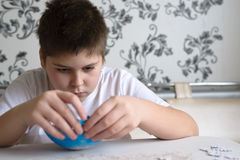 Teenager boy collects puzzles from Globe Royalty Free Stock Images