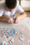 Teenager boy collects puzzles from Globe Royalty Free Stock Photography