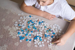 Teenager boy collects puzzles at  table Royalty Free Stock Images