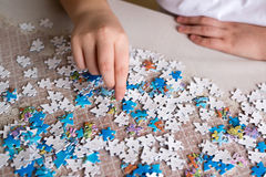 Teenager boy collects puzzles at  table Stock Photography