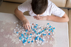 Teenager boy collects puzzles at  table Stock Images