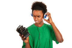 Teenager boy connecting with vintage photo camera. Teenager boy is with headphones connecting to vintage photo camera Royalty Free Stock Image