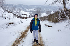 Teenager boy at countryside on wintertime. Teenage boy walking on a snowy road at countryside with village in background Royalty Free Stock Images