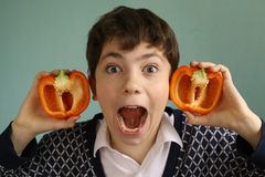 Teenager boy with cut bulgarian paprica red sweet pepper ears. Teenager boy with cut paprica red sweet pepper ears close up creative portrait Royalty Free Stock Image