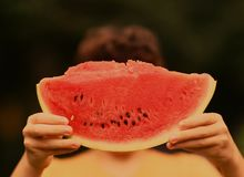 Teenager boy with cut water melon close up photo stock image