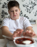 Teenager boy do not want to eat soup Royalty Free Stock Images