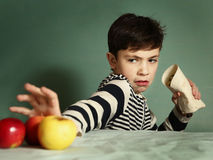 Teenager boy eat fastfood roll refuse fruit Stock Images