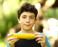 Teenager boy eating boiled corn cob close up photo stock photography