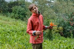 Teenager boy eating carrots. Young man eating carrots in a garden in orange jacket Stock Photo
