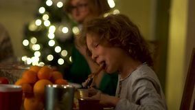 A teenager boy eats a chicken leg and wipes off his sleeve. Family Christmas Dinner. Rules of etiquette, behavior at the. Table stock video footage
