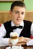 A teenager boy enjoying coffee in a cafe. Smiling teenager boy waiting for friends in a caffe in morning Stock Images