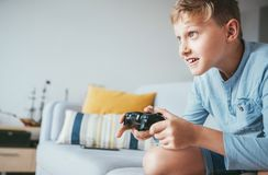Teenager boy enthusiastically plays the game console royalty free stock image