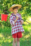 Teenager boy on fishing with rod and bucket Stock Images