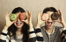 Teenager boy and girl with colored doughnuts eyes Royalty Free Stock Images