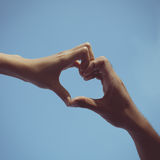 Teenager boy and girl hands in heart form love in blue sky Stock Images
