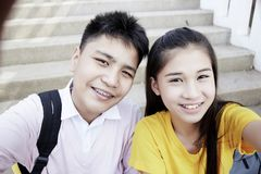 Teenager boy and girl  taking a selfie. Couple Young asian teenager boy and girl sitting on stair and taking their photo selfie by smartphone stock images
