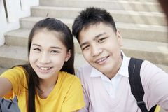 Teenager boy and girl  taking a selfie. Couple Young asian teenager boy and girl sitting on stair and taking their photo selfie by smartphone stock photography