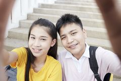 Teenager boy and girl  taking a selfie. Couple Young asian teenager boy and girl sitting on stair and taking their photo selfie by smartphone stock image