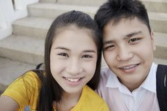 Teenager boy and girl  taking a selfie. Couple Young asian teenager boy and girl sitting on stair and taking their photo selfie by smartphone royalty free stock image