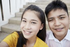 Teenager boy and girl  taking a selfie. Couple Young asian teenager boy and girl sitting on stair and taking their photo selfie by smartphone royalty free stock photos