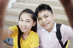 Teenager boy and girl  taking a selfie. Couple Young asian teenager boy and girl sitting on stair and taking their photo selfie by smartphone royalty free stock photo