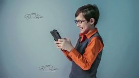 Teenager boy with glasses plays the game the race stock video