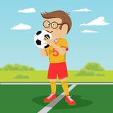 Teenager boy with glasses poses with soccer ball on field. Teenager boy with glasses poses with soccer ball on the field Royalty Free Stock Photography