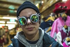 Teenager boy with a Gothic sunglasses with diffracted lens. Or Kaleidoscope in a fashion shop of Camden Lock Market or Camden Town in London, England, United royalty free stock image