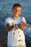 Teenager boy with handful of stones in hands Stock Photo