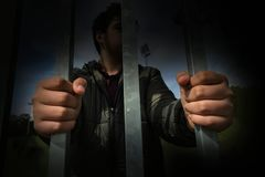 Teenager boy hands holding strong iron bars. Immigrant and refugee crisis. Dramatic border fence or prison concept. Stock photo stock image