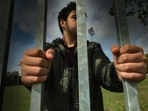 Teenager boy hands holding strong iron bars. Immigrant and refugee crisis. Seen from above. Dramatic border fence or prison concep. T - stock photo royalty free stock photo