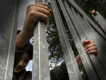 Teenager boy hands holding strong iron bars. Seen from below. Immigrant and refugee crisis. Dramatic border fence or prison concep. T - stock photo royalty free stock image