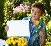 Teenager boy hold blank paper sheet with roses and flox flowers Stock Photography