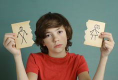 Teenager boy hold mom and dad drawing in two torn paper pieces Stock Image