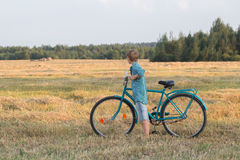 Teenager boy holding bicycle in farm field Royalty Free Stock Photos