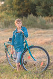 Teenager boy holding bike in farm field. Teenager boy holding a bike in farm field Stock Image