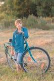 Teenager boy holding bike in farm field Stock Image