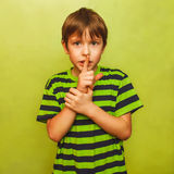 Teenager boy holding finger to his mouth silence Royalty Free Stock Photography