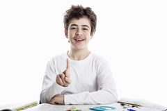 Teenager boy on homeworks smiling and showing number 1. Latin Caucasian Teenager boy sitting while doing homework is happy and shows number one sign with finger Stock Photography