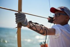 Teenager boy learns to shoot from a classic wooden bow. On the beach royalty free stock image