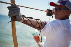 Teenager boy learns to shoot from a wooden bow. Teenager boy learns to shoot from a classic wooden bow on the beach stock images